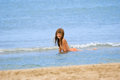The girl on a beach bathes in sea Stock Photo
