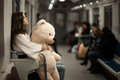 Girl with bear in a subway car sad hugged her toy and riding the background blured people are not recognizable photographs of the Stock Image