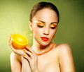 Girl with beautiful make up holding orange fruit on green background Stock Image