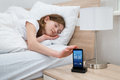Girl On Bed Snoozing Mobile Phone Alarm Royalty Free Stock Photo