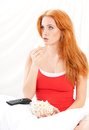 Girl on bed surprised with red hair watching tv with the bowl full of popcorn her Stock Image
