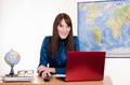 Girl behind the desk in office of travel agency young beautiful employee Royalty Free Stock Photo