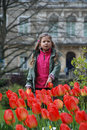 Girl behind the flower bed of red tulips a little stands at spring park bare trees and dwelling houses in background Stock Photo