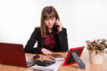 Girl behind office desk on phone listening to a friend cute business woman in the at the computer Royalty Free Stock Photography