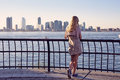 Girl on berth back view of blonde young woman leaning railing in port sunny summer day Stock Photos