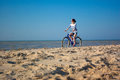 The girl with bicycle beautiful on walk at sea against blue sky Stock Photo