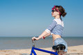 The girl with bicycle beautiful on walk at sea against blue sky Royalty Free Stock Photo