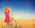 Girl with bicycle on field.