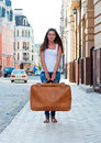 Girl with a big suitcase in the street. Stock Photo