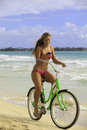 Girl on bike at beach texting Stock Photo