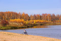 Girl with bike on lakeside a riding a in beautiful autumn day Stock Images