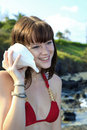 Girl in a bikini listening to a sea shell Stock Photography