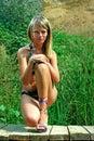 Girl in bikini on a wooden pier smilnig over reeds Stock Image