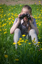 Girl with binocular on a flower meadow Stock Image