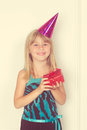 Girl with a birthday gift and cap Royalty Free Stock Photo