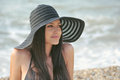 The girl in a black bathing suit beautiful sexy hat resting on sea Royalty Free Stock Photo