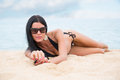 Girl in a black bathing suit lying on the sand tanned young Stock Photography