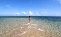 Girl in black bikini walking on the white beach Royalty Free Stock Photo