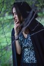 The girl with the black cloak in the forest Stock Image