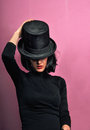 Girl in black with cylinder posing studio top hat Stock Image