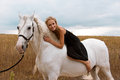 Girl in the black dress is riding on horse a white Royalty Free Stock Images