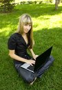 The girl in black, on the lawn with a laptop Stock Images
