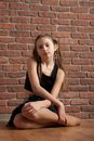 Girl in black  sitting near brick wall Royalty Free Stock Image