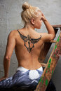 Girl with black temporary tattoo painted with paints for body art Royalty Free Stock Photo