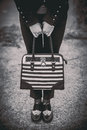 Girl with black and white bag in the hands shoes her outdoor Royalty Free Stock Images