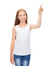 Girl in blank white shirt pointing to something design concept smiling teenage or pressing imaginary button Royalty Free Stock Images