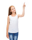 Girl in blank white shirt pointing to something design concept smiling teenage or pressing imaginary button Royalty Free Stock Photo