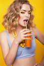Girl with blond curly hair  with bijou, holding orange bottle of beverage Royalty Free Stock Photo
