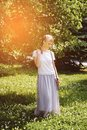 stock image of  A girl with blond hair, a white t-shirt and a long skirt, on a Sunny summer day. The young woman smiles, looking down
