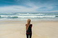 Girl with blonde dreadlocks standing on shore watching the ocean. Travel. Royalty Free Stock Photo