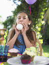 Girl blowing balloon at birthday party young up the outdoor Stock Photos