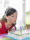 Girl blowing birthday candles closeup of a young out Royalty Free Stock Image
