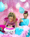 Girl blowing birthday candles out girls having fun at party while one is Stock Photos
