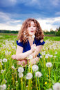 Girl blowing a dandelion Royalty Free Stock Images