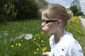 Girl blowing dandelion blond with glasses a Royalty Free Stock Photos