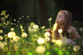 Girl blowing on a dandelion flower Royalty Free Stock Photo
