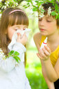 Girl is blowing her nose outdoors little brother gives nasal spray Stock Image
