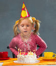 Girl blowing out candles Stock Images