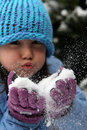 Girl blowing snow from gloves Stock Photo