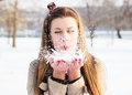 Girl blowing snow from hands winter Stock Images