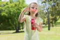 Girl blowing soap bubbles at park cute young the Royalty Free Stock Photos