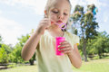 Girl blowing soap bubbles at park cute young the Royalty Free Stock Image