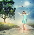Girl with Blue Butterflies at a Magical Brook Royalty Free Stock Image