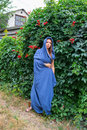 Girl in a blue cloak hooded standing on the green wall background of wild grapes Royalty Free Stock Image
