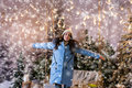 Picture : Girl in blue down jacket rejoicing because of snowing standing n noble  roses