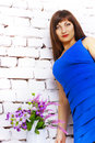 Girl in a blue dress beautiful on background of white brick wall Stock Photos